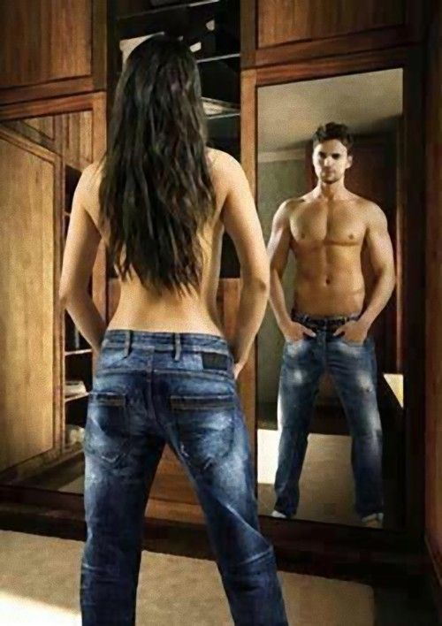 A feminine-appearing person looks into a mirror and sees a reflection of a very masculine person looking back at them.