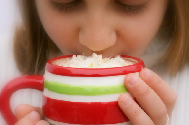 A girl sipping hot cocoa from a mug
