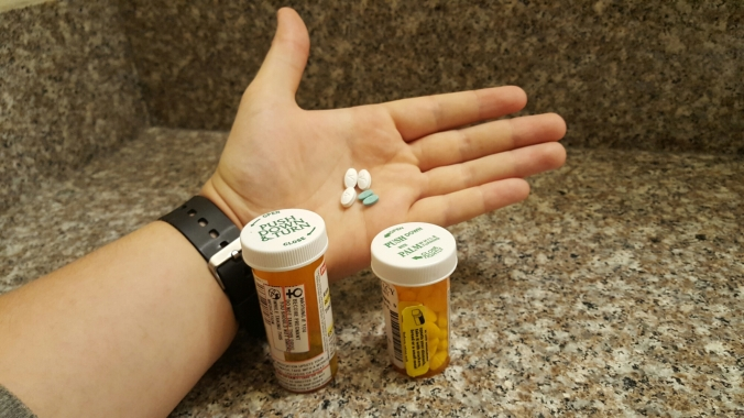 Two prescription bottles and an open palm of a hand with three white pills and two smaller blue pills.